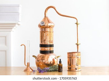 Distilling apparatus alembic with esential oil flowers at the wooden table.