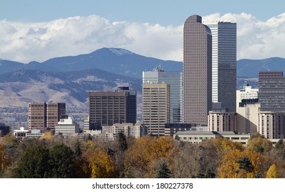 Distinctive Denver, Colorado skyscrapers, with the Rocky Mountains in the background and autumn trees in the foreground.