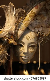 Distinctive ornate Venetian carnival white and golden mask woman face with beautiful decoration in hat with natural feather classic accessory on blurred background, vertical picture