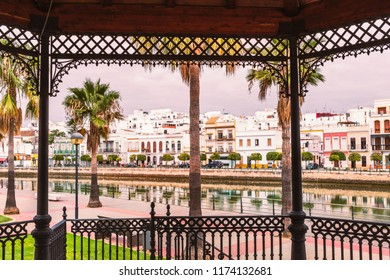 Distinctive white buildings of Ayamonte, Andlaucia, Spain along the estuary of the river Guadiana seen through the frame of a traditional band stand