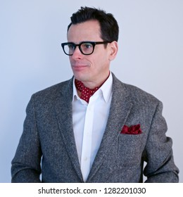 Distinguished, 40-something man with short dark hair and stylish glasses, wearing a blazer with a pocket square and an ascot.