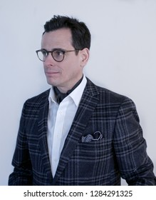 distinguished 40-something man with short dark hair and stylish glasses, wearing a blazer with a pocket square and an ascot against a light solid background