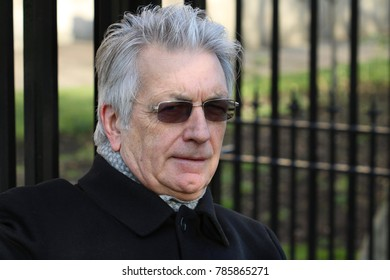 Distinguished mature man, elegantly dressed, silver hair, outdoors in Chelsea, London. December 2017.