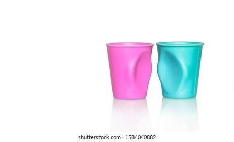 A distorted and flawed pink and a blue metallic glasses stood next to one another facing each other on white background
