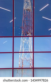 Distorted reflection of radio transmission tower with cellular communication antennas in window building. Mobile internet. Propagation of high-frequency radio waves 5G. Microwave radiation penetration