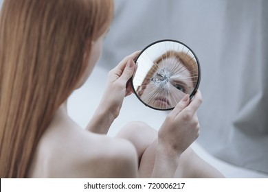 Distorted reflection of a woman in a small, broken mirror