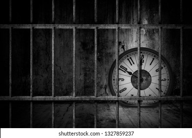 Distorted soft melting clock is imprisoned in old prison rusted metal bars with dark and dim light, concept of losing valuable time and trap in business
