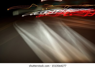 Distorted street lines and car lights at night as seen from drunk, drugged, sleepy or medicated drivers.