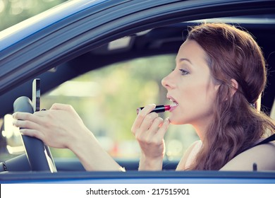 Distracted driver. Side view window view beautiful young woman applying makeup while driving car, isolated city traffic background.