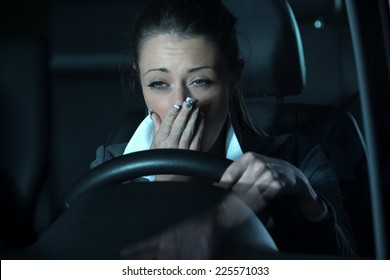 Distracted exhausted woman driving a car late at night.