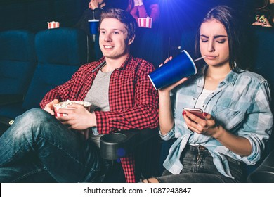 Distracted girl is watching on the phone. She is bored with watching movie. Also she is drinking coke from big and blue cup. Guy is happy and watching movie.