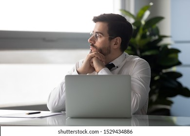 Distracted from job millennial businessman sitting at table with computer, looking aside, dreaming about vacation or holidays. Lost in thoughts company worker employee having break at office.