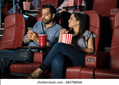 Distracted man using his phone while ignoring his date and a movie at the cinema theater