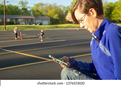 Distracted parent plays on phone while kids play in the background
