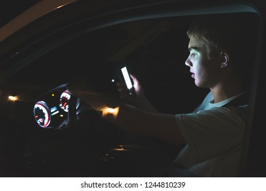 Distracted teenager driving a car with his cell phone in his hand. The light from the screen of the phone is illuminating his face.