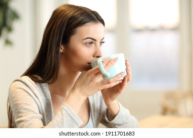 Distracted woman drinking coffee in the morning at home