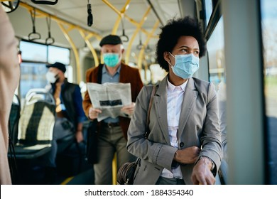 Distraught African American businesswoman wearing face mask and looking through a window while commuting to work by bus.