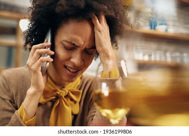 Distraught African American woman holding her head in pain while receiving bad news over cell phone.