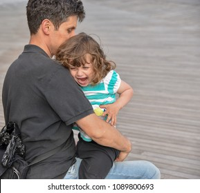 A distraught little girl cries on her father's lap