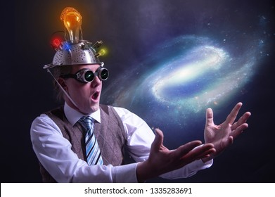 distraught looking conspiracy believer in suit with aluminum foil head holding the galaxy or universe in his hands