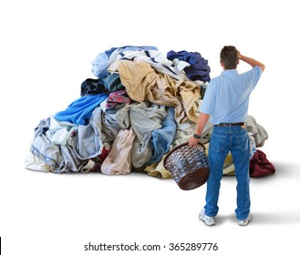 A distraught man with his hand to his head and a laundry basket in his hand is standing in front of a giant pile of dirty clothes overwhelmed by this household chore