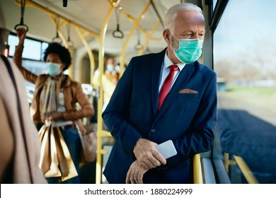 Distraught mature businessman wearing protective face mask and looking through the window while commuting by public transport.