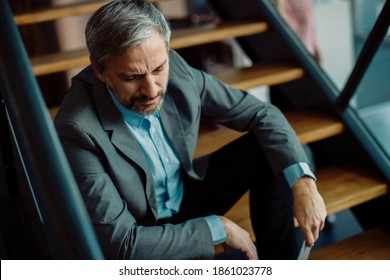 Distraught mid adult businessman sitting on the staircase in the office.