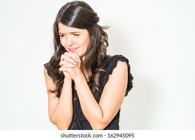Distraught tearful young woman with her hands clasped in anguish standing with downcast eyes against a white studio background