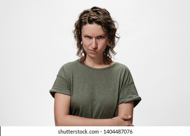 Distressed angry offended curly woman purses lips, looks with jealousy and regret, keeps hands crossed over chest, tells about unfair things, feels offended, isolated on white wall