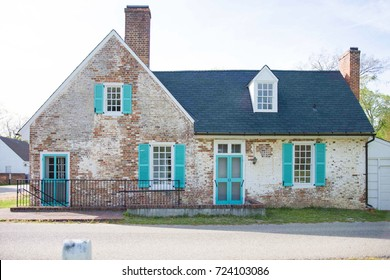 Distressed brick, bright turqoise trim, old colonial home in Yorktown Virginia, USA