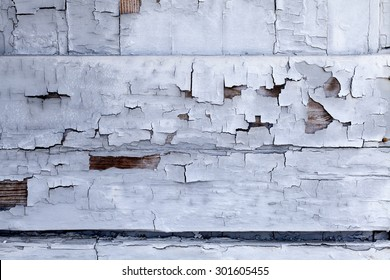 Distressed building wall with white aged paint chipping off