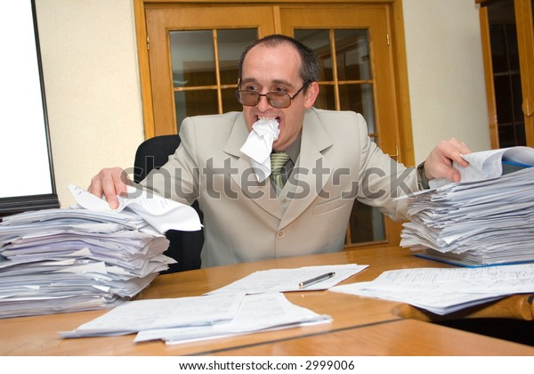 Distressed businessman eating the paperwork