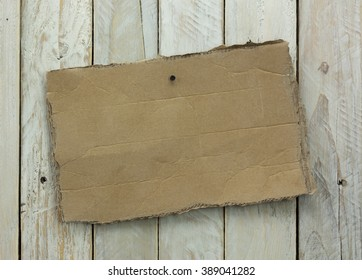 Distressed cardboard sign on a wooden background
