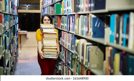 Distressed female student wandering between shelves, searching for books