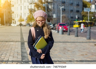 Distressed girl child with a backpack, notebooks, in a coat and french beret. Urban background.