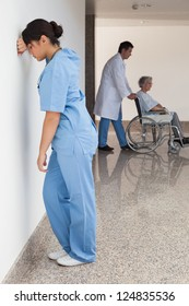 Distressed nurse standing against wall while doctor pushes patient on wheelchair