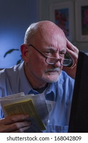 Distressed older man at computer and holding bills, vertical