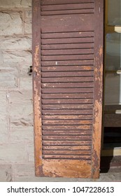 Distressed and weatherbeaten shutter painted brown on farm hosue in Karoo South Africa