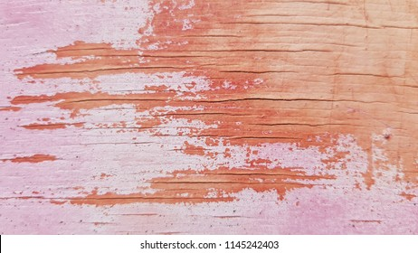 Distressed weathered plywood texture in beautiful pink coral blushing palette. Cracked painted plywood surface closeup. Shabby background.