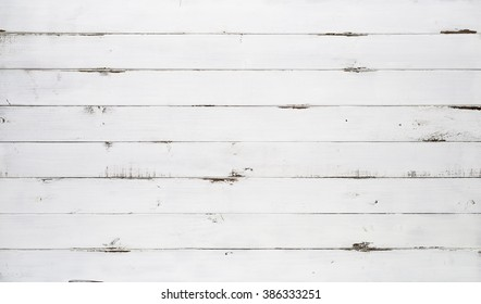 Distressed white wood texture background viewed from above. The wooden planks are stacked horizontally and have a worn look. This surface would be great as design element for a wall, floor, table etc.