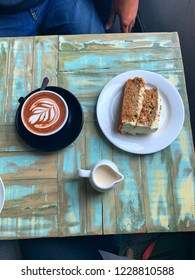Distressed wood table in hipster arty coffee shop, organic carrot cake, latte art on hot chocolate, jug of lactose free soya milk