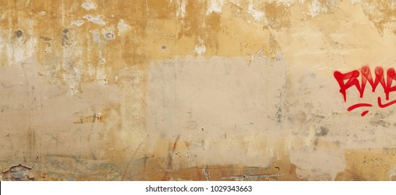 Distressed Yellow Brown Old Brick Wall With Graffiti Street Art. Background And Painted Lines And Draw. Abstract Grunge Modern Grafitty Wallpaper. Abstract Plastered Wall Web Banner. Design Element.