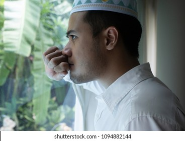 A distressed young Thai muslim man, wearing the traditional taqiyah, standing in front of a window, looking outside