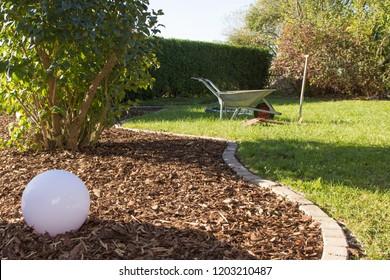 Distribute bark mulch on the wayside