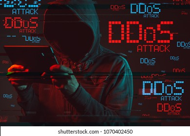 Distributed denial of service or DDoS attack concept with faceless hooded male person using tablet computer, low key red and blue lit image and digital glitch effect