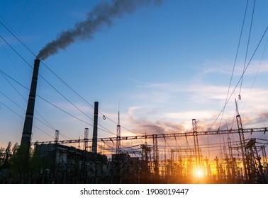distribution electric substation with power lines and transformers, at sunset.
