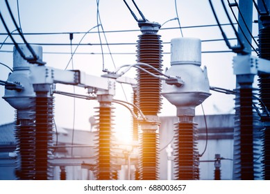 distribution electric substation with power lines and transformers, at sunset