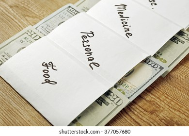 Distribution of money, financial planning, dollars in envelopes, on wooden table background