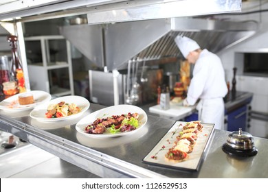 the distribution table in the kitchen of the restaurant. the chef prepares a meal on the background of the finished dishes.