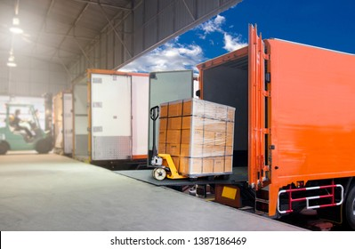 Distribution warehouse and Logistics, freight industry transport by truck. Forklift loading cargo into a truck, trucks docking at warehouse